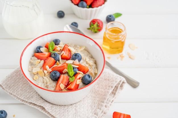 Schüssel haferflocken-porridge mit blaubeeren, erdbeeren, mandelblüten und honig