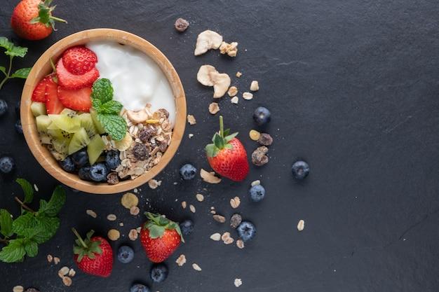 Schüssel hafergranola mit joghurt, frischen blaubeeren, erdbeeren, kiwi-minze und nussbrett für gesundes frühstück, draufsicht, kopienraum, flache lage. gesundes frühstücksmenükonzept. auf dem schwarzen felsen