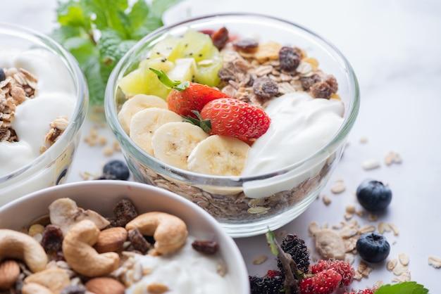 Schüssel hafergranola mit joghurt, frischen blaubeeren, maulbeeren, erdbeeren, kiwi, banane, minze und nussbrett für gesundes frühstück, draufsicht, kopienraum, flache lage. vegetarisches lebensmittelkonzept.