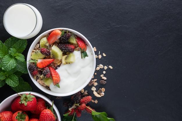 Schüssel hafergranola mit joghurt, frischer maulbeere, erdbeeren, kiwi-minze und nüssen auf dem schwarzen felsenbrett für gesundes frühstück, draufsicht, kopienraum, flache lage. gesundes frühstücksmenükonzept.