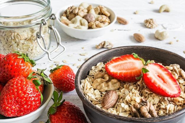 Schüssel hafermüsli mit erdbeere, müsli und nüssen auf rustikalem holztisch