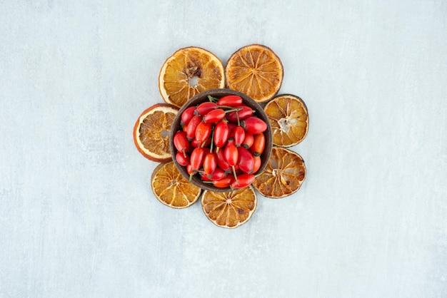 Schüssel hagebutten und getrocknete orangenscheiben auf steinoberfläche.