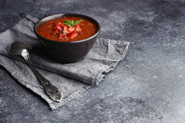 Schüssel hausgemachte gazpacho-suppe. weinleselöffel auf grauem handtuch neben schüssel mit kalter würziger tomatensuppe.