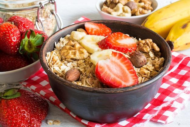 Schüssel hausgemachtes obstmüsli mit erdbeere, banane und nüssen