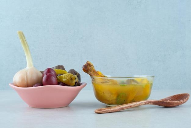 Schüssel hühnersuppe und schüssel fermentiertes gemüse.