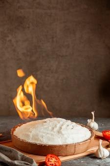Schüssel in brennendem salz mit tomaten und knoblauch bedeckt