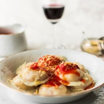 Schüssel italienische ravioliteigwaren mit würziger tomatensauce und käse