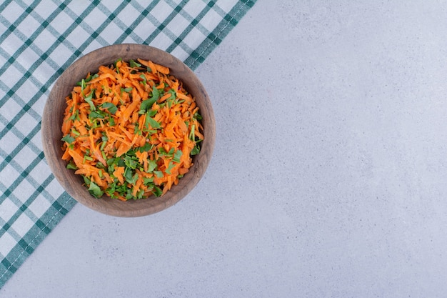 Schüssel karottensalat auf einer tischdecke auf marmorhintergrund.
