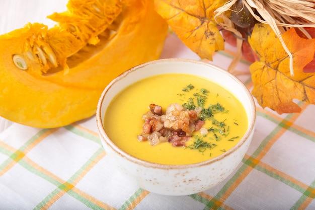 Schüssel kürbissuppe mit gebratenen zwiebeln und speck
