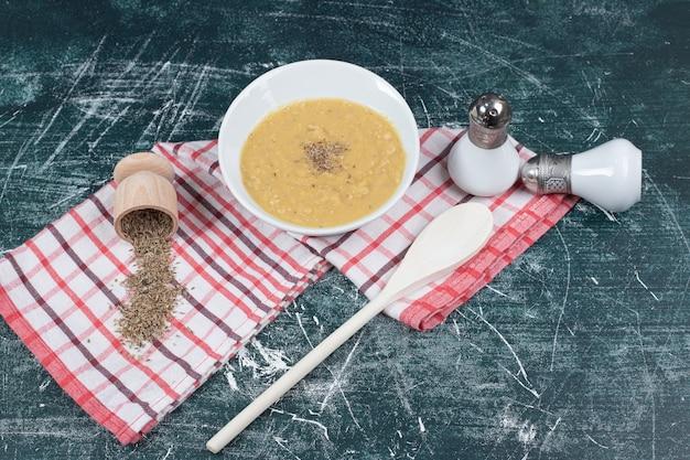 Schüssel linsensuppe, salz, gewürze und tischdecke auf marmorhintergrund. hochwertiges foto