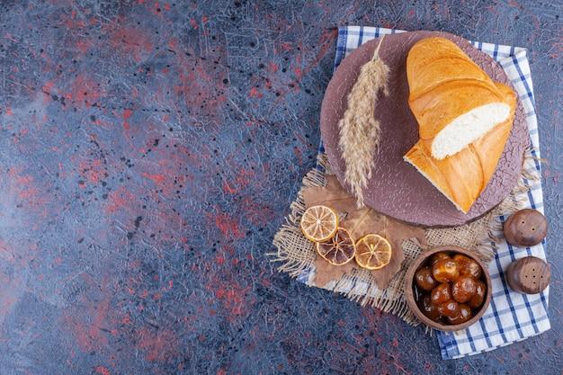 Schüssel marmelade und brot auf einem brett auf einem geschirrtuch, auf dem blau.