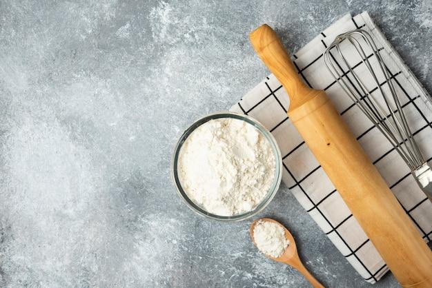 Schüssel mehl, eier und küchenutensilien auf marmoroberfläche.
