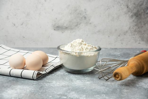 Schüssel mehl, eier und küchenutensilien auf marmortisch.