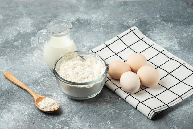 Schüssel mehl, eier und milch auf marmor.