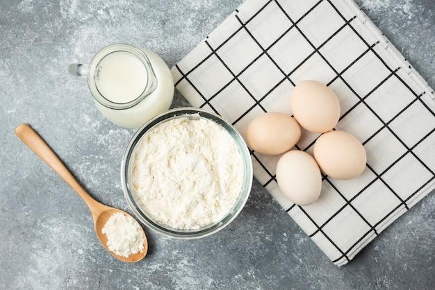 Schüssel mehl, eier und milch auf marmoroberfläche.