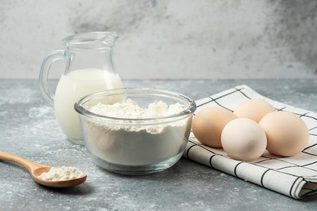 Schüssel mehl, eier und milch auf marmortisch.