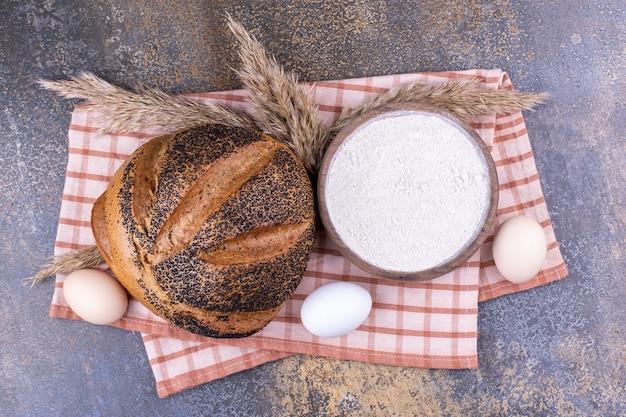 Schüssel mehl eier und sesam überzogenes brot auf einem handtuch auf marmoroberfläche