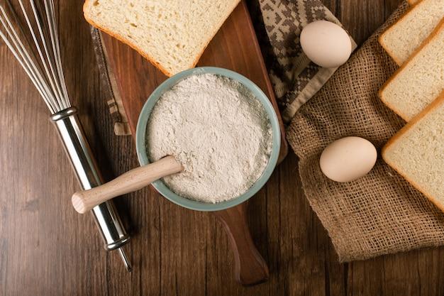 Schüssel mehl mit eiern und scheiben brot