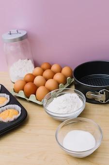 Schüssel mehl; zucker; eier; cupcake und backform auf hölzernen schreibtisch vor rosa hintergrund