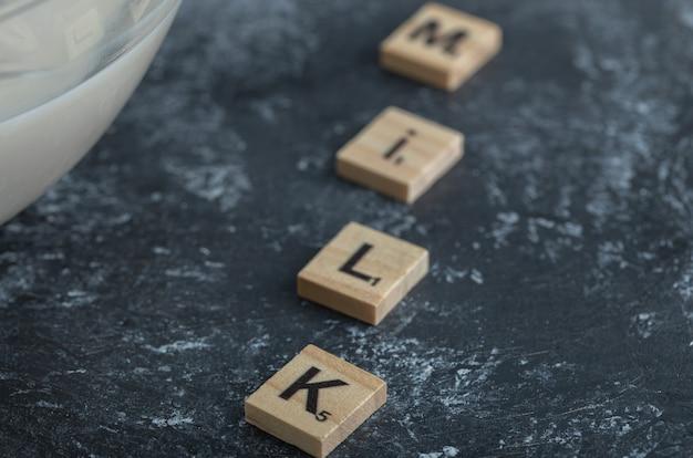 Schüssel milch und holzbuchstaben als milch geschrieben.