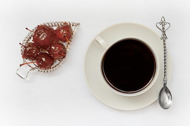 Schüssel mit apfelmarmelade, dessert, einer tasse mit einem getränk auf einer untertasse und einem silbernen löffel auf einem weißen hintergrund.