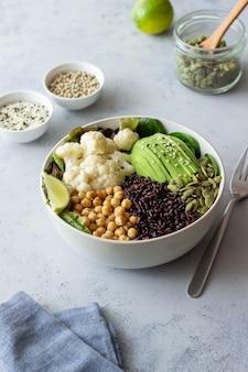 Schüssel mit avocado, schwarzem reis, kichererbsen, kohl, spinat und salat. gesundes essen. vegetarisches essen.