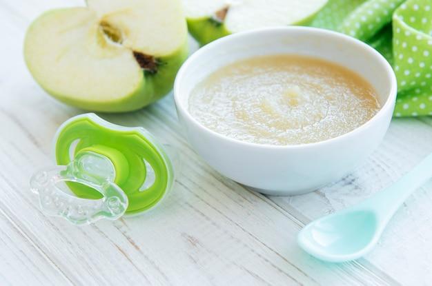 Schüssel mit babynahrung und äpfeln auf dem tisch