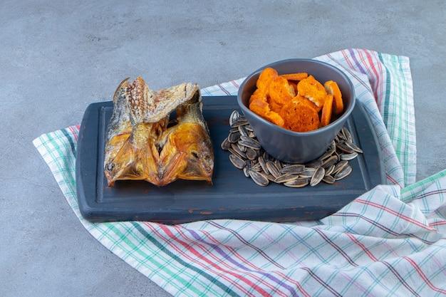 Schüssel mit brotchips, getrocknetem fisch und samen auf einem tablett auf einem handtuch, auf der marmoroberfläche.