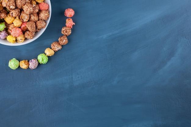 Schüssel mit bunten müslikugeln auf einem blau platziert.