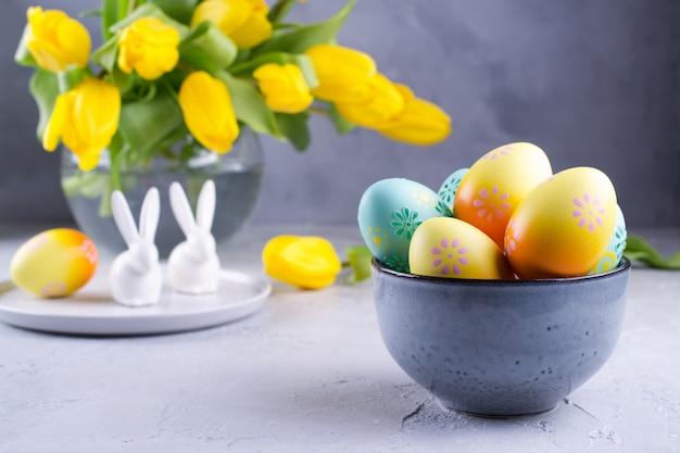 Schüssel mit bunten ostereiern; frühlings-osterndekoration auf grauem tisch mit strauß gelber tulpenblüten in glasvase; ostern innendekoration