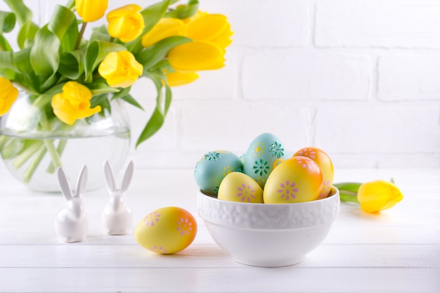 Schüssel mit bunten ostereiern, frühlings-osterndekoration auf weißem holztisch mit strauß gelber tulpenblumen in glasvase auf weißem hintergrund. ostern innendekoration