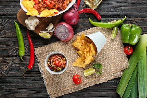 Schüssel mit chili con carne und nachos auf dem tisch