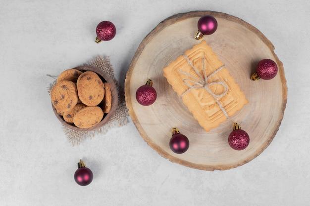 Schüssel mit chip-keksen, keksen und weihnachtskugeln auf weißem tisch. hochwertiges foto