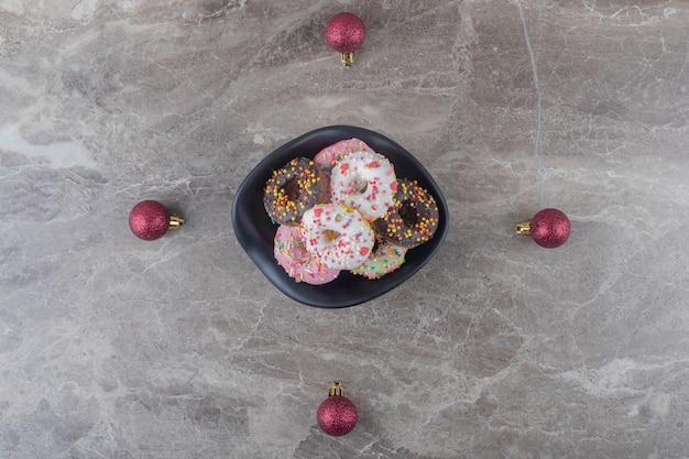 Schüssel mit donuts und weihnachtskugeln auf marmoroberfläche