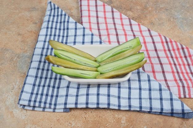 Schüssel mit eingelegten und frischen gurkenscheiben auf tischdecken