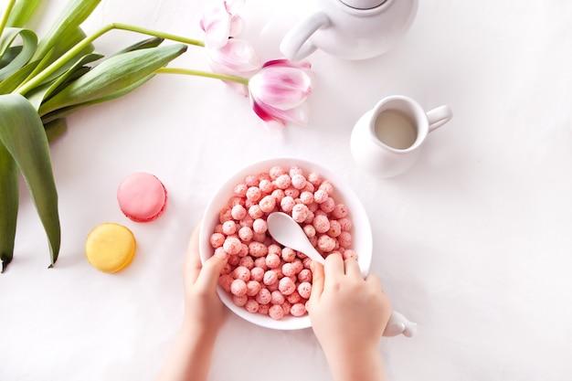 Schüssel mit erdbeer-zuckermais-kugeln. leckeres und gesundes frühstücksflocken. kinderhand nehmen einen löffel und essen.