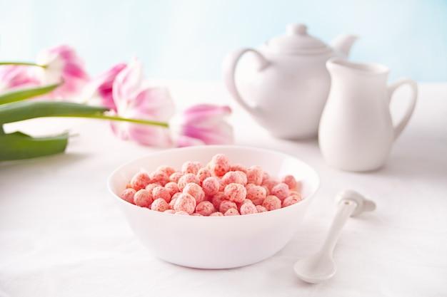 Schüssel mit erdbeer-zuckermais-kugeln. leckeres und gesundes frühstücksflocken.