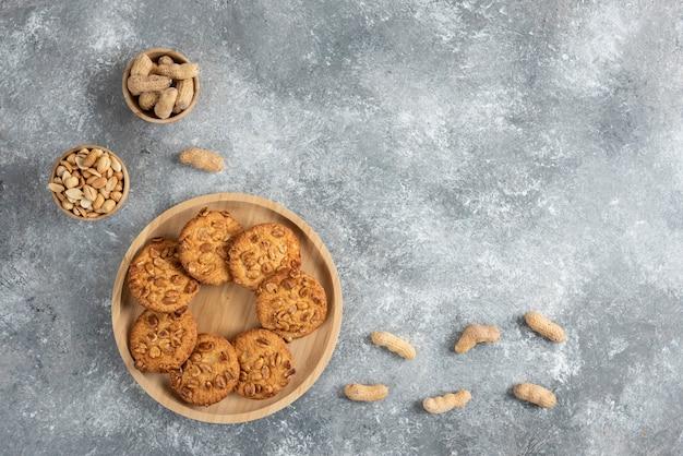 Schüssel mit erdnüssen und keksen mit bio-erdnüssen auf marmortisch.
