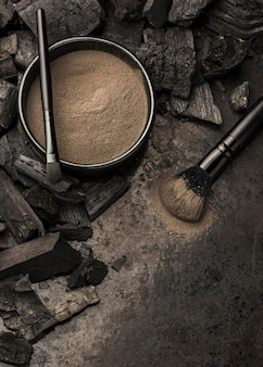 Schüssel mit feinem pulver und holzkohle neben dem pinsel