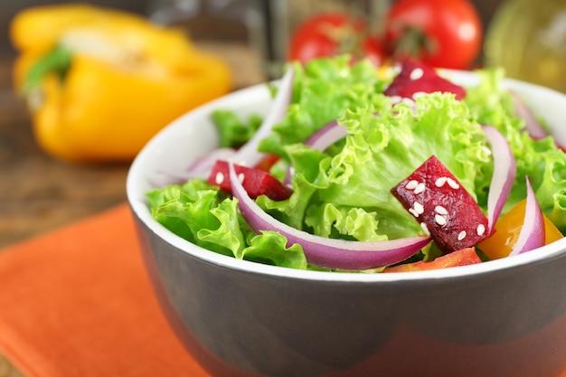 Schüssel mit frischem grünem salat auf tisch mit serviette, nahaufnahme