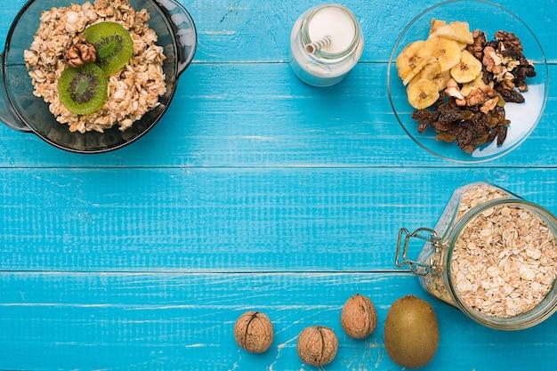 Schüssel mit frischem haferbrei mit kiwi und nüssen auf einem rustikalen tisch in blaugrün, warmes und gesundes essen zum frühstück. ansicht von oben. platz kopieren