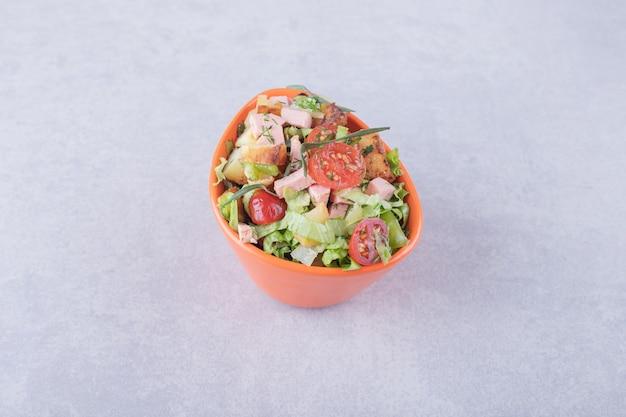 Schüssel mit frischem salat mit würstchen auf marmorhintergrund.