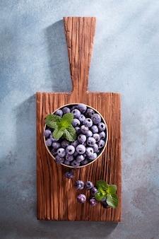 Schüssel mit frischen blaubeeren auf rustikalem holzbrett. bio-lebensmittel blaubeeren und minzblätter für einen gesunden lebensstil.