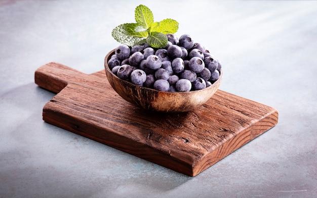Schüssel mit frischen blaubeeren auf rustikalem holzbrett. bio-lebensmittel blaubeeren und minze für einen gesunden lebensstil.