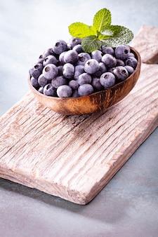 Schüssel mit frischen blaubeeren auf rustikalem holzbrett. bio-lebensmittel-heidelbeeren und minzblätter für einen gesunden lebensstil.