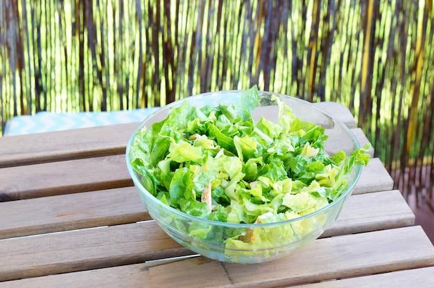Schüssel mit frischen grünen salatblättern auf einem holztisch