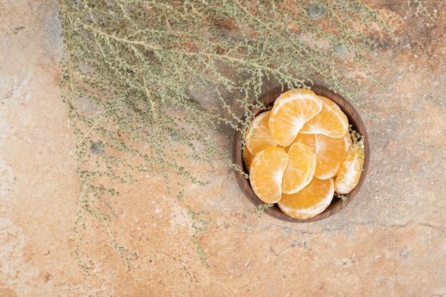 Schüssel mit frischen mandarinensegmenten auf marmorhintergrund.