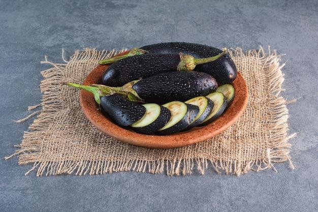 Schüssel mit frischen reifen auberginen und scheiben auf steinhintergrund.