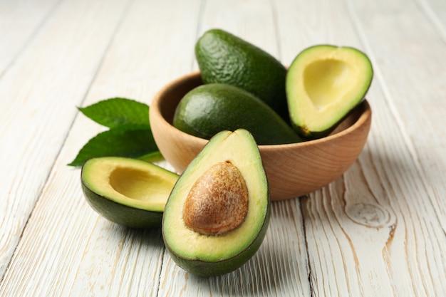Schüssel mit frischer avocado auf hölzernem hintergrund, nahaufnahme