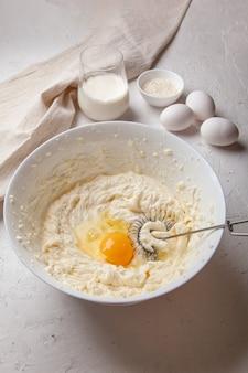 Schüssel mit frischkäse und ei zum kneten von teig. zutaten zum kochen baskisch gebrannter saint sebastian käsekuchen. frischkäse, zucker, eier, mehl und sahne. rezept schritt für schritt.
